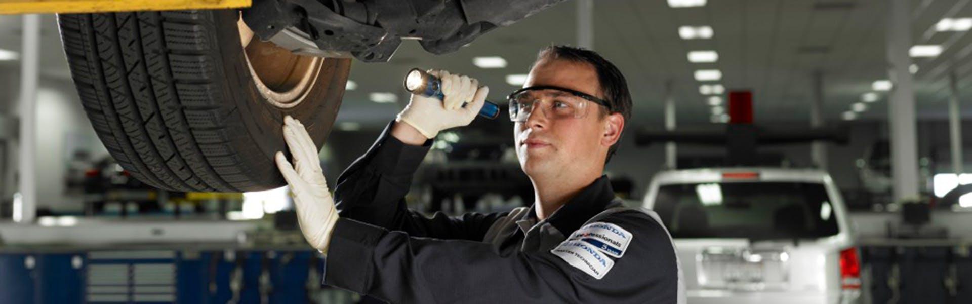 Washington Honda is a Honda Dealership in Washington near Bethel Park PA | Honda Service Advisor Replacing Tire on Honda Vehicle