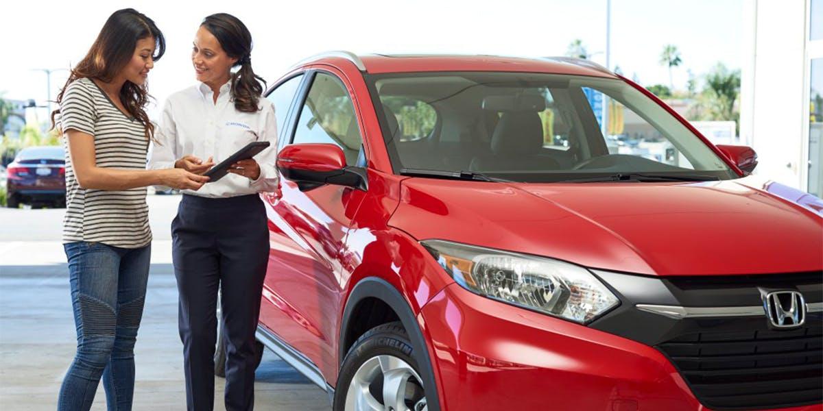 Washington Honda is a Honda Dealership in Washington near Bethel Park PA | Sales Advisor and Customer Talking While They Stand Next to Red Honda HR-V