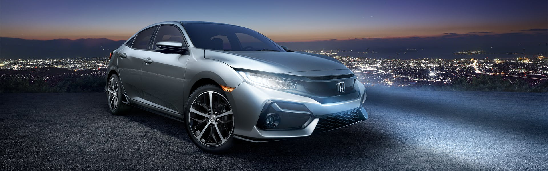 Washington Honda is a Honda Dealership in Washington near Bethel Park PA | Silver 2020 Honda Civic Hatchback Parked on Cliffside at Night with Headlights On