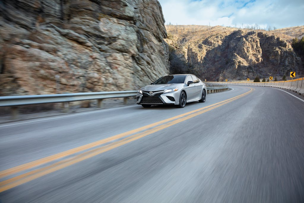 South Hills Toyota is a Toyota Dealership in Canonsburg near Thompsonville PA | Silver 2020 Toyota Camry driving on mountain road