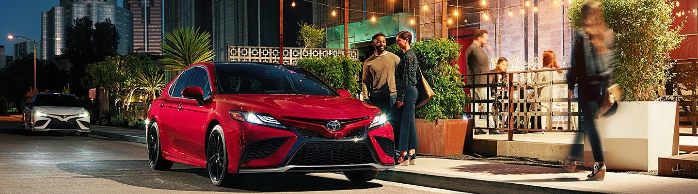 toyota camry - red exterior - parked in front of restaurant