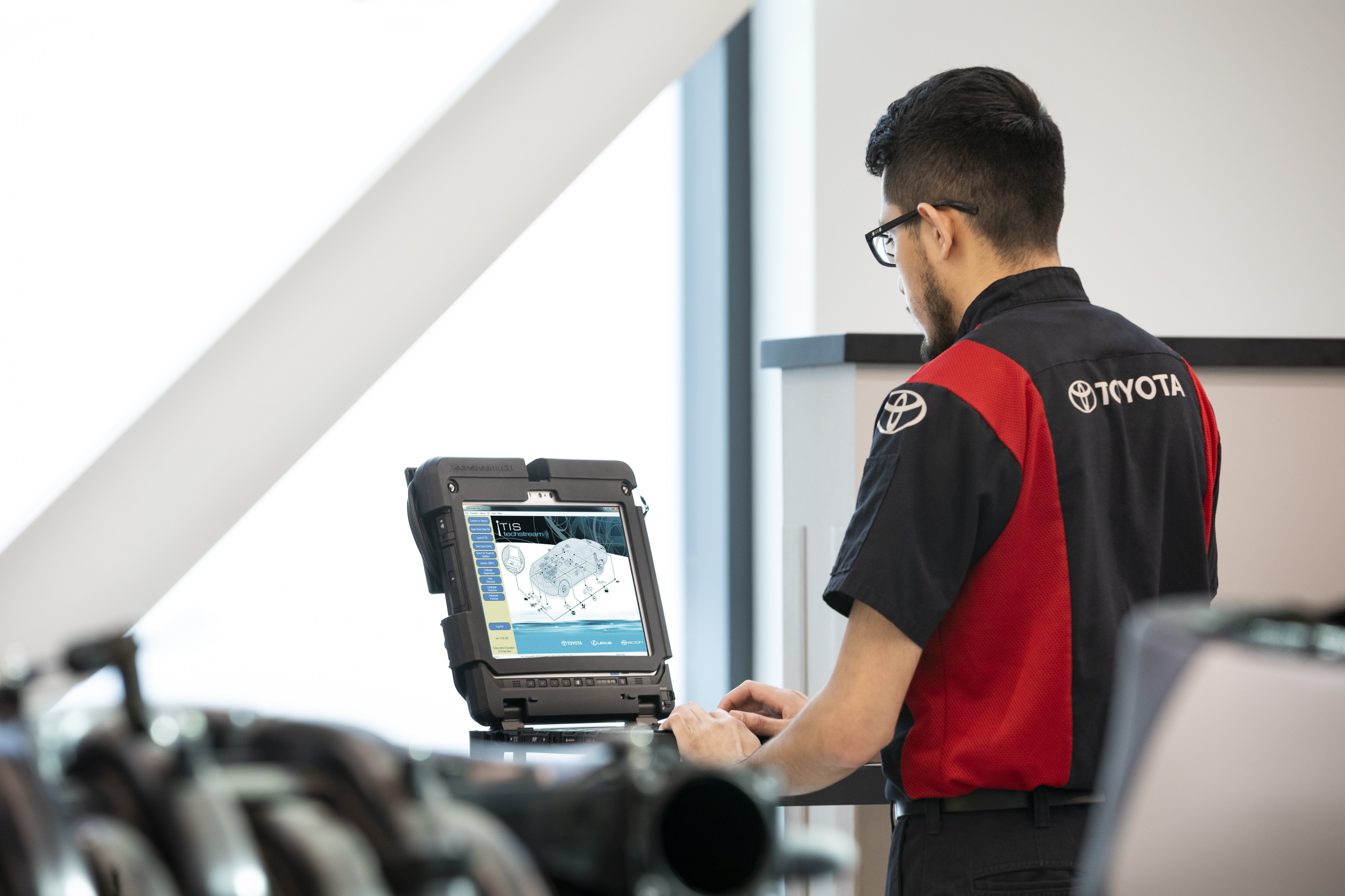 South Hills Toyota is a Toyota Dealership in Canonsburg near Pittsburgh PA | Toyota Service Technician typing on laptop in Toyota Service Center