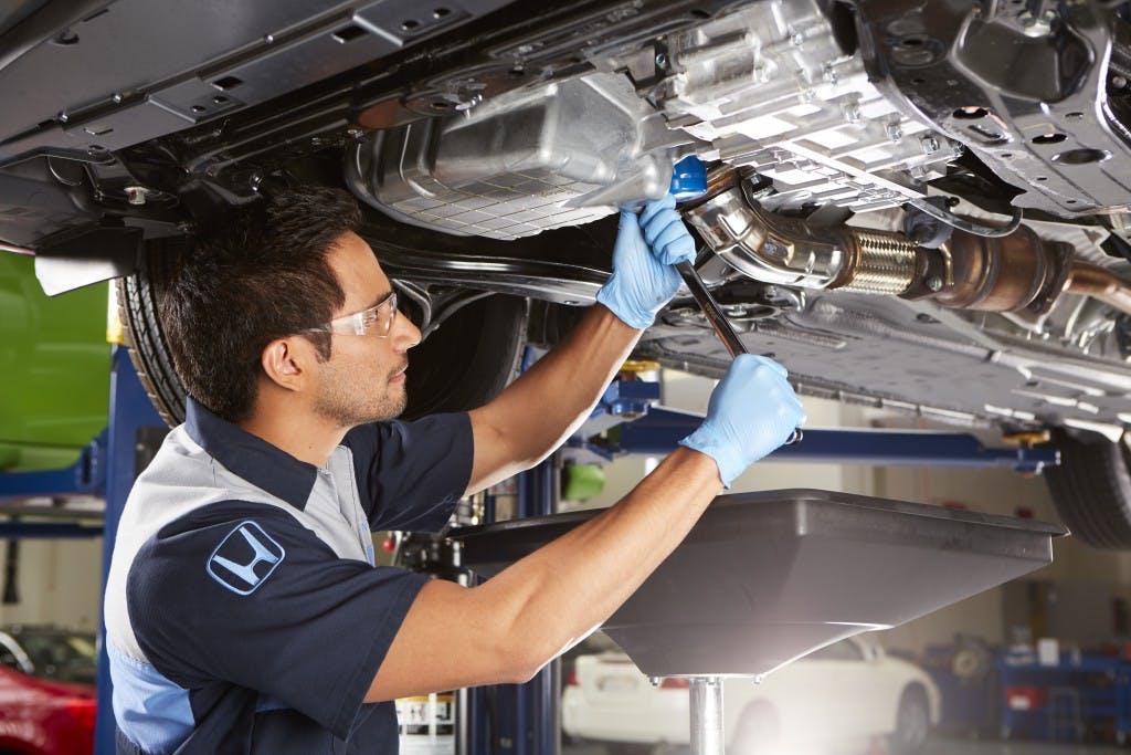 Washington Honda is a Honda Dealership near Wolfdale, PA | Honda mechanic working underneath of vehicle