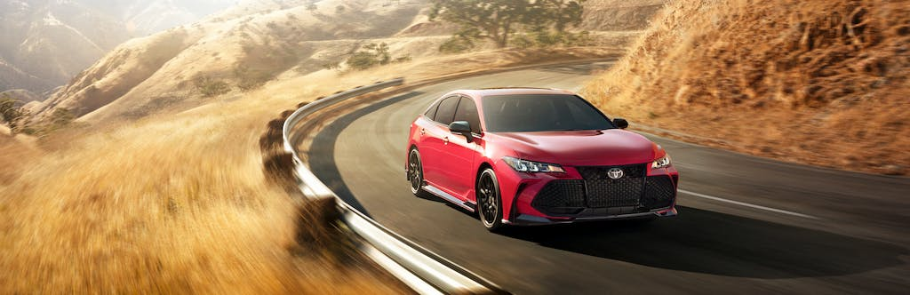 South Hills Toyota is a Toyota Dealership in Canonsburg near Thompsonville PA | Red 2020 Toyota Avalon driving on country road