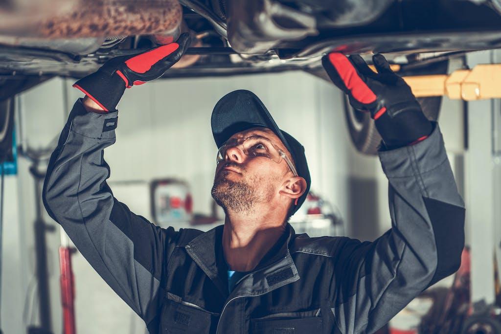 Washington Honda is a Honda Dealership near California, PA | Honda mechanic inspecting underneath of vehicle