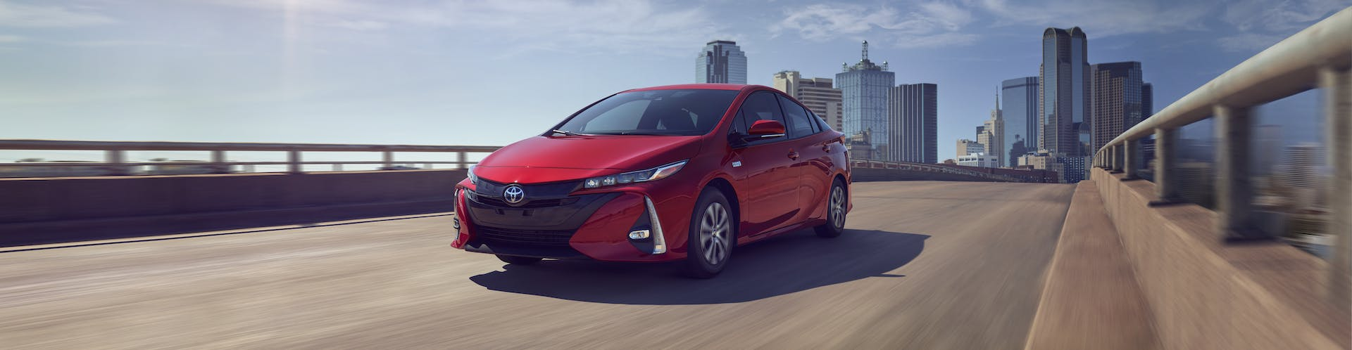 South Hills Toyota is a Toyota Dealership in Canonsburg near Pittsburgh PA | 2021 Toyota Prius Prime driving away from city