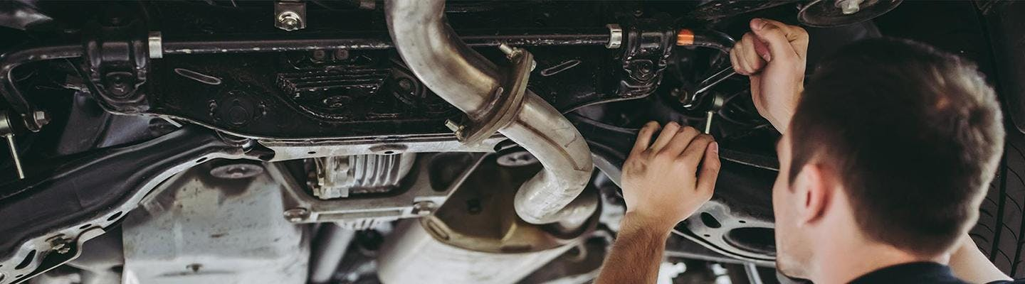 Service tech under a Toyota doing repairs
